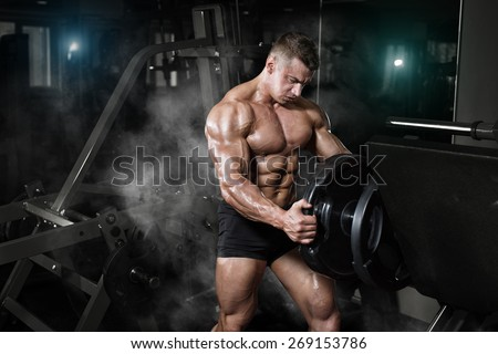 Bodybuilder muscle Athlete training with weight in gym - stock photo