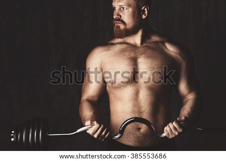 Bodybuilder. Muscular man lifting weights over dark background. Sports / Fitness / Bodybuilding. - stock photo