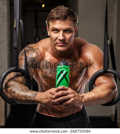 Bodybuilder on a rest with bottle of water - stock photo