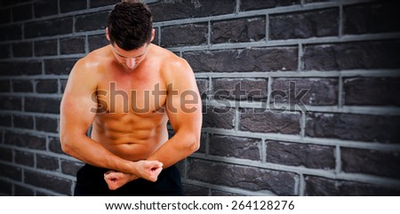 Bodybuilder posing against red brick wall