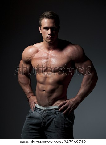 bodybuilder posing. Handsome power athletic guy male. Fitness muscular body on black background - stock photo