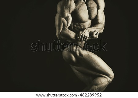 Bodybuilder posing in different poses demonstrating their muscles. Failure on a dark background. Male showing muscles straining. Beautiful muscular body athlete.