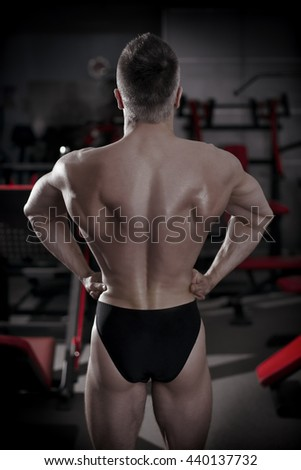 Bodybuilder posing in gym. Perfect muscular male back. Toning image - stock photo