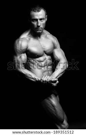 Bodybuilder posing on black background. - stock photo