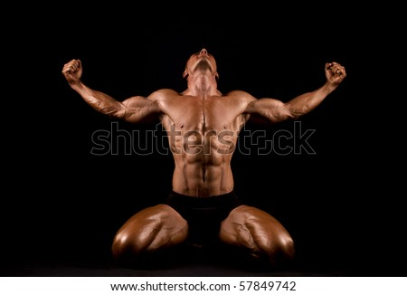 Bodybuilder posing on black background.
