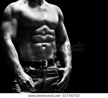 Bodybuilder posing on the black background - stock photo