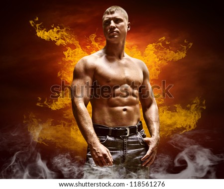 Bodybuilder posing on the fire flames background - stock photo