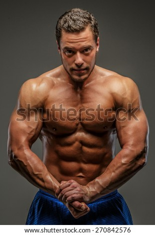 Bodybuilder showing his muscles. Isolated on grey - stock photo