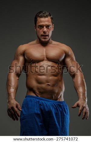 Bodybuilder shows his muscle in studio. Isolated on grey background