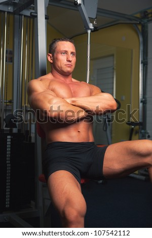 Bodybuilder sits in his training room