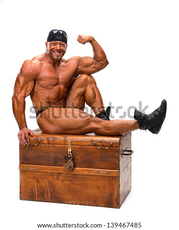Bodybuilder sitting on a wooden chest on a white background
