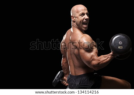 Bodybuilder sitting on workout bench in gym with barbell looking into camera isolated on black - stock photo