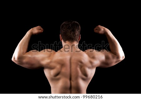 bodybuilder strong athletic muscle man, sport guy showing his male muscles, standing back over black background - stock photo