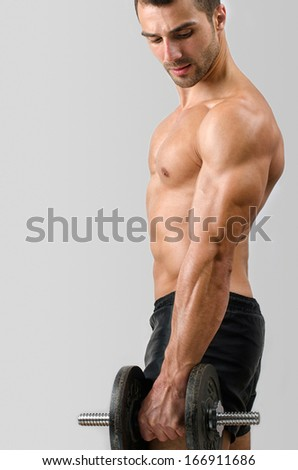 Bodybuilder training with heavy dumbbell. Strong man with perfect abs, shoulders,biceps, triceps and chest. Isolated on white background - stock photo