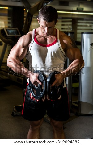 Bodybuilder trains the muscles in the gym. Fitness training. Advertising male body beautiful - stock photo