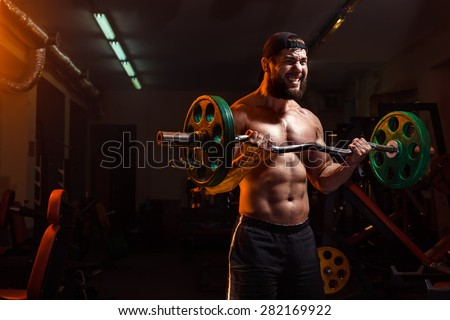 bodybuilder with beard in the gym exercising barbell - stock photo