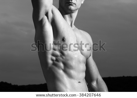 Bodybuilder with beautiful brawny bare muscular torso covered with drops of sweat on natural background, black and white, horizontal photo - stock photo