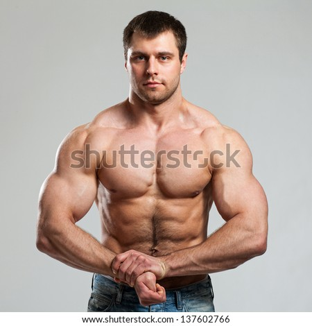 Bodybuilder with naked torso shows his biceps - stock photo