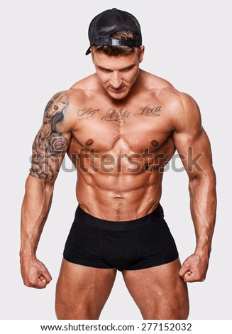 Bodybuilder with tattooes isolated on white background