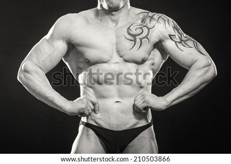 Bodybuilder with tattoos poses on a black background. Man showing his muscles. Bodybuilding, strength, muscle pose. - The concept of a sports lifestyle. Articles about bodybuilding and sports. - stock photo