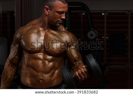 Bodybuilder Working Out Biceps - Dumbbell Concentration Curls - Best Exercise For Bicep - stock photo