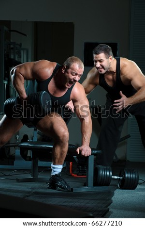 Bodybuilders training hard in gym - stock photo