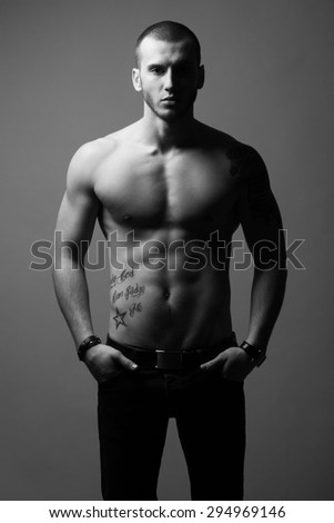 Bodybuilding and body sculpture concept. Beautiful (handsome) muscular male model with perfect body posing over gray background. Hands in pockets. Deep shadows. Black and white, monochrome studio shot - stock photo