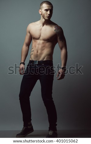 Bodybuilding, body sculpture concept. Male model with perfect body posing over gray background. Deep shadows. Full length portrait. Street style. Studio shot - stock photo