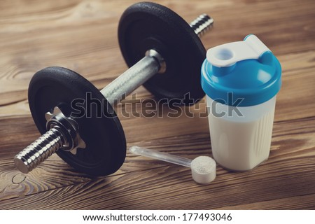 Bodybuilding components: protein shake with a dumbbell - stock photo
