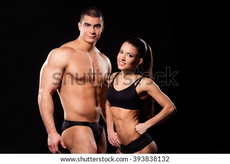 Bodybuilding couple posing and smiling. Young attractive fitness couple smiling. Photo for a magazine. Job in fitness industry.
