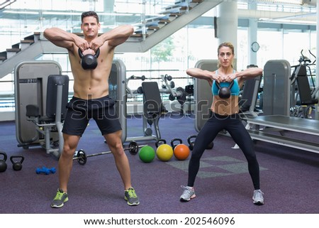 Bodybuilding man and woman lifting kettlebells at the gym - stock photo