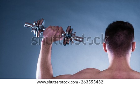 Bodybuilding. Strong fit man exercising with dumbbells. Closeup muscular young guy lifting weights rear view blue background - stock photo