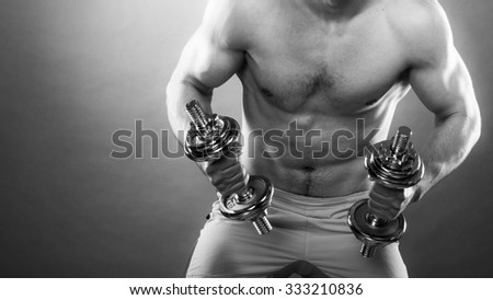 Bodybuilding. Strong fit man exercising with dumbbells. Closeup muscular young guy lifting weights black & white photo - stock photo