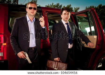 bodyguard and his boss leave the car - stock photo