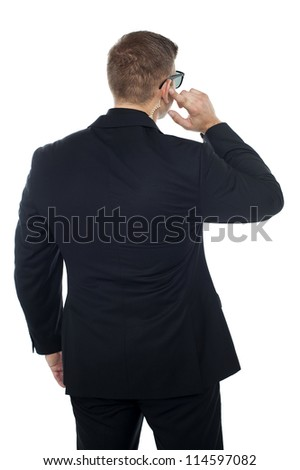 Bodyguard listening to vital information carefully while holding his earpiece. Back pose - stock photo