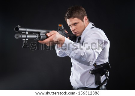 Bodyguard. Serious young man in shirt and tie holding gun and aiming somewhere while standing against black background - stock photo