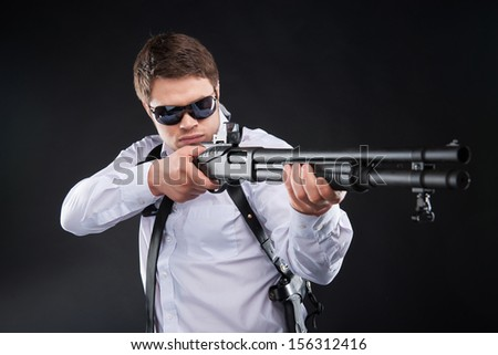 Bodyguard. Serious young man in sunglasses holding gun and aiming somewhere while standing against black background - stock photo