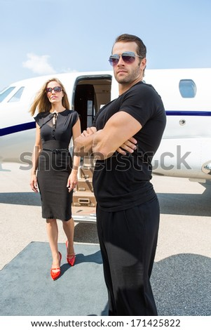 Bodyguard with arms crossed standing against elegant woman and private jet - stock photo