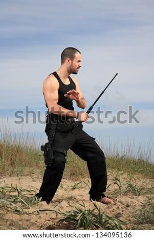 bodyguard with black uniform and a crowbar - stock photo
