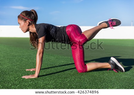 Bodyweight exercises - fitness woman doing fire hydrants legs kickbacks. Active girl training glute muscles raising one leg to the side and back for strength training in outdoor gym on grass floor. - stock photo