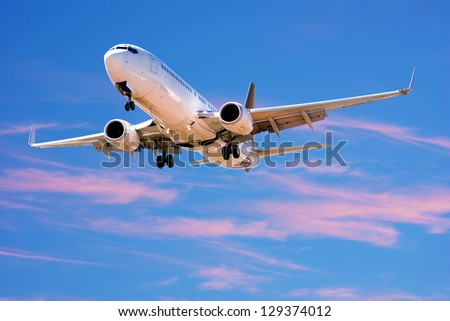 Boeing 737 landing from bright twilight sky. - stock photo
