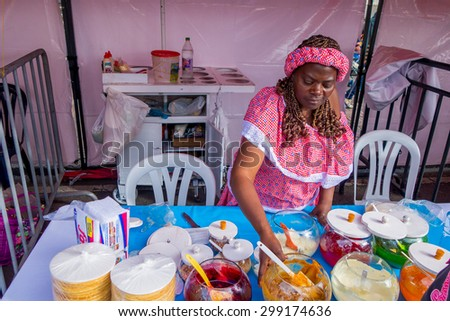 BOGOTA, COLOMBIA - FEBRUARY 25, 2015: Closeup traditional Colombian streetsnack oblea being prepared adding white sauce with top of jam and coco by lady on street in Bogota, Colombia - stock photo