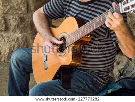 bohemian performer playing spanish guitar in a street - stock photo