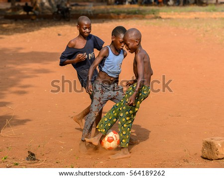 BOHICON, BENIN - JAN 11, 2017: Unidentified Beninese little boy shows football tricks with bare feet. Soccer is very popular game among the  African kids
