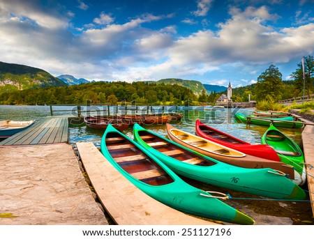 Bohinj Lake with boats and Church of St John the Baptist, Triglav National Park, Julian Alps, Slovenia. - stock photo
