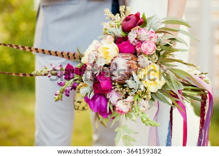 Boho bouquet in brides hands - stock photo