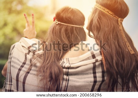 Boho female friends with blanket looking on sunset - stock photo