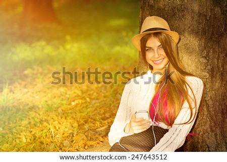 Boho styled teenage girl with smartphone. Young woman with straw hat, sweater, brown pink hair, headphones and cellphone smiling sitting in park in summer. - stock photo