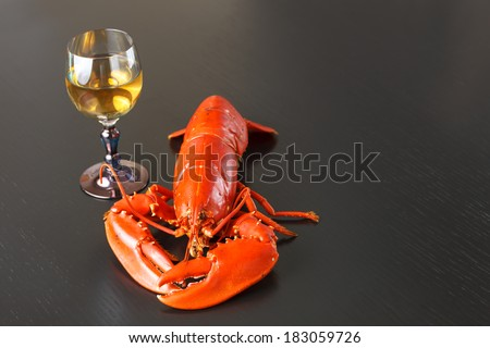 Boiled Atlantic Lobster with glass of white wine on dark wooden table. - stock photo