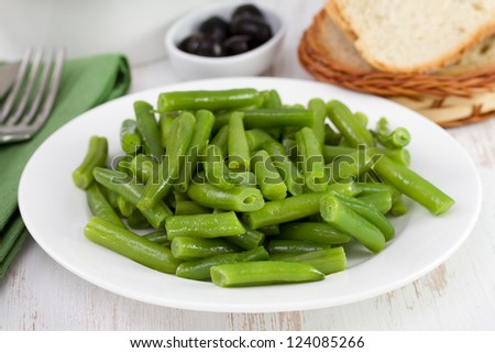 boiled beans on the plate with olives and bread